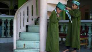 A young Muslim boy helps his friend to put on a turban at a mosque in Ampang, suburbs of Kuala Lumpur on July 11, 2013.