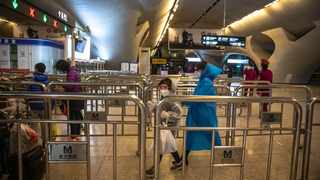 A young girl with a woman wearing protective outfit walk to the subway after arriving at the railway station in Wuhan, China Piture: EPA-EFE/ROMAN PILIPEY