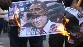 """Activists burn a poster depicting former US President George Bush disguised as current US President Barack Obama during a protest against potential US strikes on Syria, near the US embassy in Awkar, north of Beirut, September 7, 2013. US officials ordered non-emergency personnel and their family members out of Lebanon on Friday """"due to threats,"""" the US embassy in Beirut said in statement."""