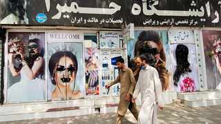 Afghan men walk past the billboard of a beauty saloon with defaced posters of models in Kabul, Afghanistan. Fighting and violence have significantly reduced in Afghanistan with the surrender of the government troops and the resounding victory of the Taliban. Picture: EPA-EFE/Stringer
