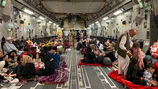 Afghan people sit inside a U S military aircraft to leave Afghanistan, at the military airport in Kabul on August 19, 2021 after Taliban's military takeover of Afghanistan. (Photo by Shakib RAHMANI / AFP)