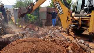 An excavator demolishes a toilet where the remains of Nancy Majonhi's husband had been hidden for six years. Picture: SAPS.