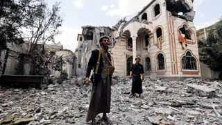 Armed Yemenis stand amid the ruins of the house of an army commander loyal to the Houthis after it was hit by two airstrikes in Sanaa.  EPA/YAHYA ARHAB