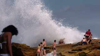 Beachgoers face heavy waves crashing onto rocks by a sea pool adjacent to Coogee Beach Wednesday, January 11, 2006 in Sydney, Australia. Australian authorities evacuated beaches in Sydney and the southern coast of New South Wales state after shark sightings yesterday. Authorities ordered swimmers out of the water in Sydney's Tamarama and Bronte beaches yesterday, the beach next to Coogee, according to a police statement. Photographer: JACK ATLEY/Bloomberg