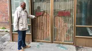 Bevil Lucas shows the door that police knocked down to gain entrance to the Woodstock Hospital building. Picture: Tariro Washinyira/GroundUp