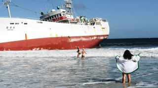 Cape Town. 120514. Peter Womsley, Wendy Prevost and Rene De Wet tease the seamen aboard the r beached fishing long liner Eihatsu Maru at Clilfton First Beach. Photo by Michael Walker