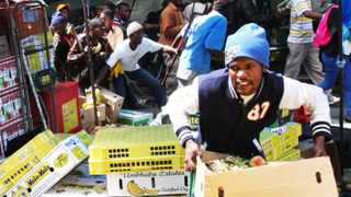 Cape Town-131030. Various communities marched to the Provincial Legislature this afternoon demanding to see Zille about housing demands. She did not appear and a number of impatient marchers marched through the CBD looting stalls and the like. these protesters are seen looting a fruit stand just outside the ABSA buildingl .Reporter: Daneel Knoetze. Photo: jason boud