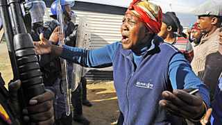 Cape Town 140602- A woman from Siyanyanzela informal settlement in Lwandle cries in front of the police after they illegally evicted them . Picture Cindy waxa.Reporter Argus
