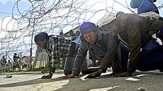Cape Town 140602- People crawls under the bob wire to get their belongings during the evictioni at Siyanyanzela informal settlement in Lwandle . Picture Cindy waxa.Reporter Argus