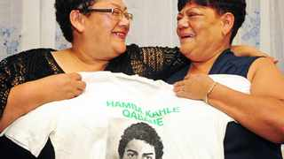 """Cape Town - 160315 - Ashley Kriel's sisters, Michel Assure (right) and Melanie Adams (left), pose with a t-shirt bearing his image. Ashley Kriel was shot at a house in Hazendal, Athlone on July 9, 1987, with security police claiming his death was an """"accident"""". The National Prosecuting Authority (NPA) may finally re-open the case. Picture: David Ritchie"""