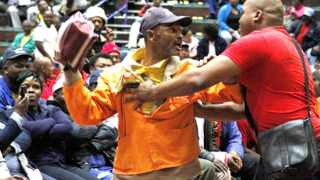 Capetown-140729-An angry man who was one of the municipality workers who attended the meeting that was heldin Goodhope Center was escorted out of Building-Picture by Bheki Radebe