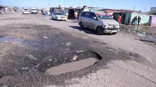 Cars navigate their way through potholes in Emms Drive in Philippi. Picture: Ayanda Ndamane/African News Agency (ANA)
