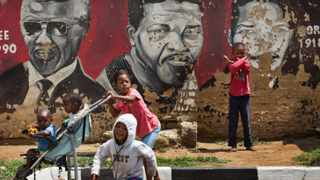 Children walk past a mural depicting Nelson Mandela during different stages of his history. Photo: Ben Curtis
