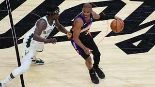 Chris Paul #3 of the Phoenix Suns dribbles the ball while Jrue Holiday #21 of the Milwaukee Bucks. Photo: Michael Gonzales/Getty Images via AFP