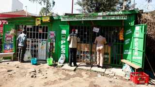 Customers are seen at mobile money transfers kiosks, known as M-Pesa agents, near Ngong township in the outskirts of Kenya's capital Nairobi. Picture: Reuters