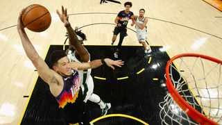 Devin Booker #1 of the Phoenix Suns goes up for a slam dunk ahead of Jrue Holiday #21 of the Milwaukee Bucks. Photo: Christian Petersen/Getty Images via AFP