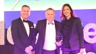 During a gala ceremony at the Villa Marina's Royal Hall in Douglas, the sought-after award was presented to Chief Executive of Standard Bank Isle of Man Limited, Chris Till, by host, television presenter Julia Bradbury, and Craig Mitchell, director of sponsors Browne Craine & Co. Image: Supplied.
