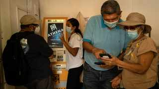 Employees and artisans from the Artesanal Market of San Salvador arrive at the Bitcoin automated teller machine in El Zonte, El Salvador. Picture: Bloomberg/Cristina Baussan