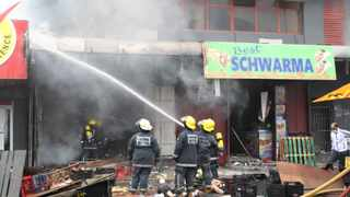Ethekwwini firefighters douse the flames of an inferno at shop that was torched in the Durban CBD on Monday. Picture: Doctor Ngcobo/African News Agency(ANA)