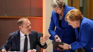 European Council President Donald Tusk, left looks on as Britain's Prime minister Theresa May, center left, and Germany's Chancellor Angela Merkel, right, look at a tablet ahead of a pre-dinner meeting during an EU summit at the Europa building in Brussels. Picture: Kenzo Tribouillard, Pool Photo via AP