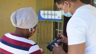 FILE – An IEC official sanitises a voter's hands, scans her ID before she voted at Alfonso Primary School in Paarl. 11.11.20. File photo: Henk Kruger/African News Agency (ANA)