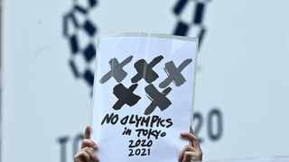 """FILE - An anti-Olympic activist holds a paper of """"no Olympics in Tokyo 2020 2021"""" in a protest outside the metropolitan government building, 30 days before the Olympic Games opening ceremonies, in Tokyo. Photo: Philip Fong/AFP"""