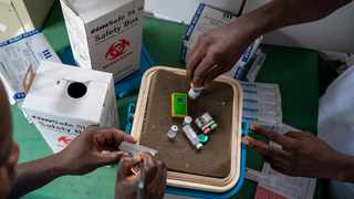 FILE – Health officials prepare to vaccine residents of the Malawi village of Migowi, where young children become test subjects for the world's first vaccine against malaria. 10.12.19. (AP Photo/Jerome Delay)
