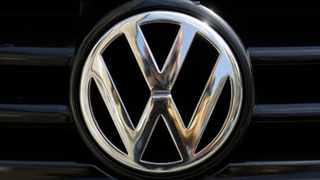 FILE - In this Aug. 1, 2017 file photo the car marques badge of Volkswagen, VW, is photographed on a car in Berlin, Germany. Despite only 66 electric vehicles sales in SA last year, VW is considering introducing electric vehicles into the Rwanda market. (AP Photo/Markus Schreiber, file)
