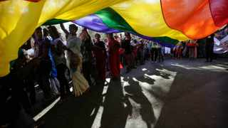 """FILE- In this Jan. 28, 2012 file photograph, participants carry a rainbow flag during a gay, lesbian, bisexual and transgender parade in Mumbai, India.A lawyer for India's Home Ministry told the country's top court Thursday that gay sex was """"immoral"""" and urged the court to keep it illegal, even as the government denied it opposed decriminalizing homosexuality. (AP Photo/Rajanish Kakade, file)"""