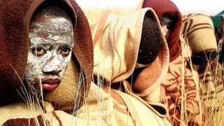 FILE - In this photo taken Saturday, June 30, 2013 A Xhosa boy covered with a blanket and smeared with chalky mud sits in a field as he and others  undergo traditional Xhosa male circumcision ceremonies into manhood near the home of former South African president Nelson Mandela in Qunu, South Africa. At least 60 males have died at initiation schools in eastern South Africa since the start of the initiation season in May, health officials confirmed. Thirty of them died in the Eastern Cape in the last six weeks, and 300 others were hospitalized with injuries. (AP Photo/Schalk van Zuydam, File)