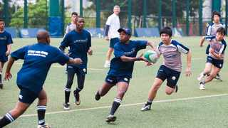 FILE - Laureus World Sports Academy Members Morne du Plessis and Sean Fitzpatrick with youngsters from two Laureus-supported rugby-based projects in Hong Kong and South Africa. Photo: Victor Fraile/Getty Images for Laureus