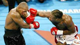 FILE - Lennox Lewis lands a solid right jab on Mike Tyson during round seven of their WBC/IBF/IBO World Heavyweight Championship bout at the Pyramid Arena in Memphis, Tennessee, June 8, 2002. Lewis defeated Tyson by a knockout in the eighth round to retain his championship titles. Photo: Jeff J Mitchell/Reuters
