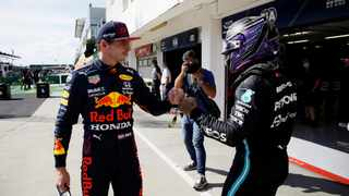 FILE - Mercedes' Lewis Hamilton bumps fists with Red Bull's Max Verstappen after qualifying in pole position and third place respectively at the Hungarian GP. Photo: David W Cerny/AFP