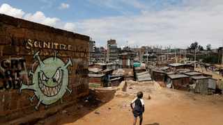 FILE PHOTO: A boy walks in front of graffiti promoting the fight against the coronavirus disease in the Mathare slums of Nairobi. REUTERS/Baz Ratner