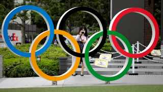 FILE PHOTO: A woman wearing a protective mask amid the coronavirus disease (COVID-19) outbreak, takes a picture of the Olympic rings in front of the National Stadium in Tokyo, Japan October 14, 2020. REUTERS/Kim Kyung-Hoon/File Photo