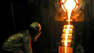 FILE PHOTO: A worker pours gold at the AngloGold Ashanti mine at Obuasi, Ghana