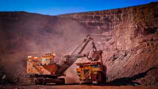 FILE PHOTO: An excavator loads iron ore into a haul truck at the Sishen open cast mine, operated by Kumba Iron Ore Ltd. Photographer: Nadine Hutton/Bloomberg