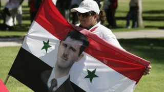Fadia Abouseibaa holds a Syrian flag with an image of Syrian President Bashar al-Assad during an anti-war rally in Los Angeles, California September 7, 2013. US President Barack Obama appealed on Saturday to a dubious American public to back his bid to use military force in Syria while supporters scrambled to persuade lawmakers to authorize the move.