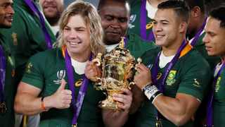 Faf de Klerk and Cheslin Kolbe pose with the Webb Ellis Cup following the Springboks' Rugby World Cup triumph. Matthew Childs/Reuters