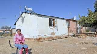 Family member Sheila Jacobs sits on the chair where the deceased used to sit in front of the house she lived in. Picture: Picture: Danie van der Lith/DFA