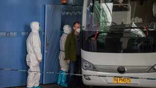 File photo: A member of the World Health Organization (WHO) team investigating the origins of the Covid-19 pandemic boards a bus following their arrival at a cordoned-off section in the international arrivals area at the airport in Wuhan. Picture: AFP