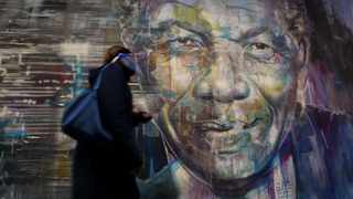 File photo. A woman walks past a mural of late former president Nelson Mandela. File photo: Brendan Magaar/African News Agency(ANA)