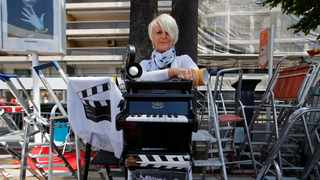 File photo: Cinema fan Martine Santoro, 61, from Cannes, poses next to a toy piano rigged up to the front of her stepladder in homage to The Piano director Jane Campion. Picture: Reuters