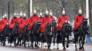 File photo: Soldiers of the Life Guards ride through the snow on the Mall in London. Photo: AP