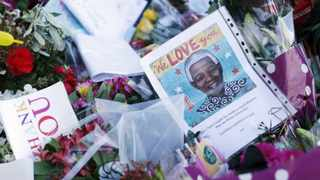 Flowers and notes left at the foot of the statue of former South African president Nelson Mandela are seen in Parliament Square in London. Picture: Olivia Harris