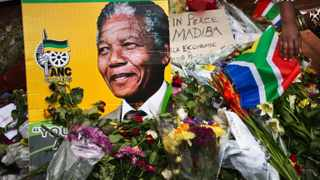 Flowers, posters, and messages left by mourners lie in front of Nelson Mandela's old house in Soweto. Picture: Ben Curtis