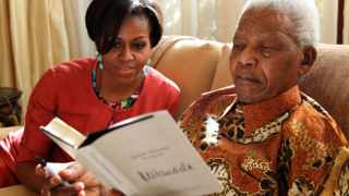 Former president Nelson Mandela is seen with US first lady Michelle Obama as they view his newest book titled Nelson Mandela by Himself at his home in Houghton, Johannesburg. Photo: Sapa