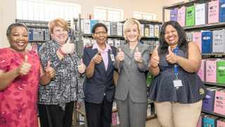 From left: Dr Zuki Pinini, Chief Director of NDOH HIV/Aids and STIs; Amy Herman-Roloff, US CDC Country Director; Facility Manager Sister Nancy Nkopane; Ambassador-designate Lana Marks; and Gloria Maimela, of WRHI, view the new Laudium CHC filing system.