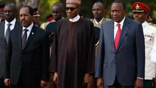 From left, Somalian President Hassan Sheikh Mohamoud, Nigerian President Muhammadu Buhari and Kenyan president Uhuru Kenyatta stand for the national anthem at the fallen heroes monument at Moi Barracks during an interreligious prayer meeting for the Kenyan soldiers who were killed in an attack on their base by Somalia's Islamist militant group al-Shabab, in Eldoret, Kenya, on January 27, 2016. Picture: EPA/DANIEL IRUNGU