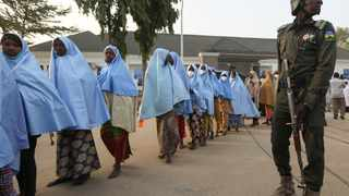 Girls who were kidnapped from a boarding school in the northwest Nigerian state of Zamfara, walk in line after their release, as a police officer stands close in Zamfara, Nigeria. Photo: Afolabi Sotunde/Reuters